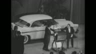 At the 'Imperial Ball A Night in Monte Carlo' Prince Rainier spins the handle of a hopper and his fiancee Grace Kelly opens it to remove the winner...