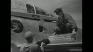 At Yokota Air Base near Tokyo US Korean War pilot standing on wing of airplane removes component from side of plane while mechanic looks on / pilot...