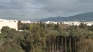 Athens cityscape with forests buildings hills clouds sunshine / Long shot Mount Lycabettus with grey clouds behind pull out to Greek Parliament...