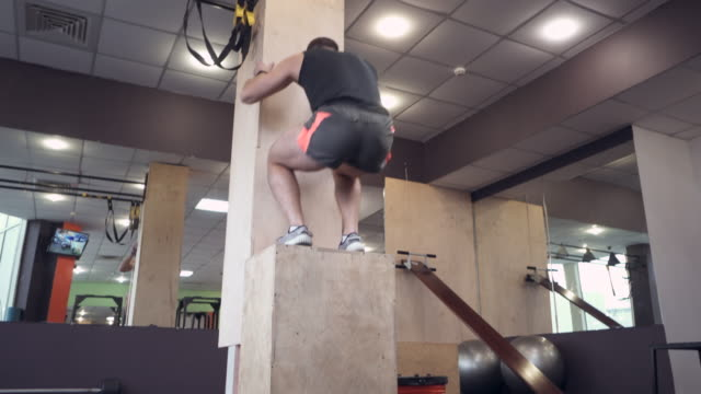 Athlete jumping on wooden box at gym