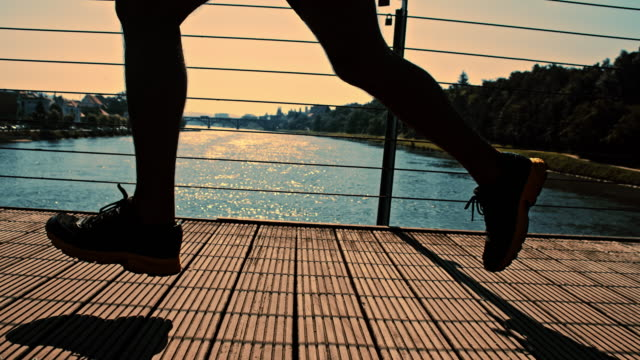 SLO MO Athlete running across the bridge at dusk