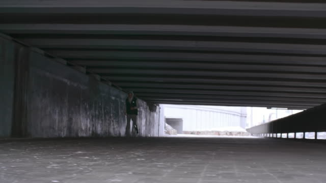 Athlete with fitness prosthesis running under bridge