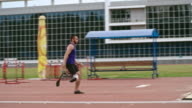 Athlete with prosthetic leg practicing long jump