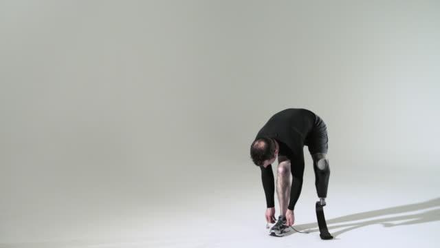 Athlete with prosthetic leg tying shoelace