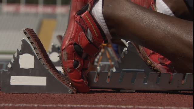 CU Athletes adjusting feet into track starting blocks / Sheffield, England, UK