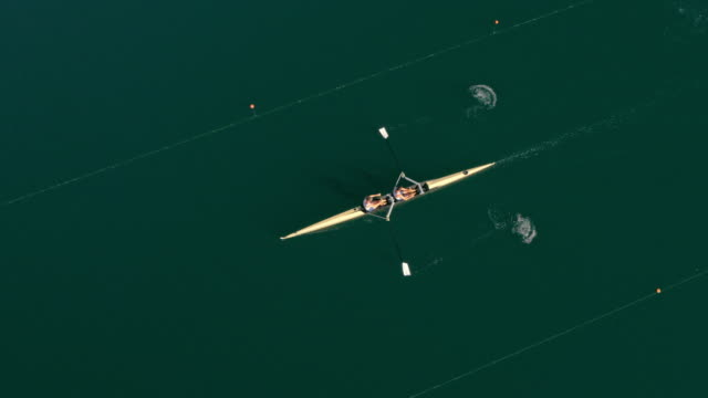 AERIAL Athletes rowing in a coxless pair across a lake on a sunny day