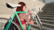 Athletic woman with red hair carrying bike up steps and pushing bike in city