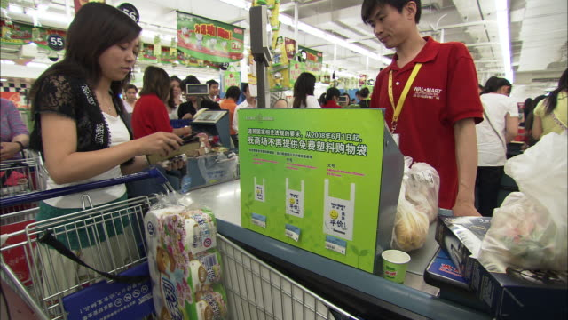MS SELECTIVE FOCUS Attendant and customer at cash registers in supermarket, Beijing, China