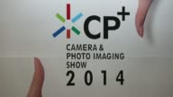 Attendees arrive at the CP Camera and Photo Imaging Show in Yokohama Kanagawa Prefecture Japan on Thursday Feb 13 People walk past a sign for the CP...