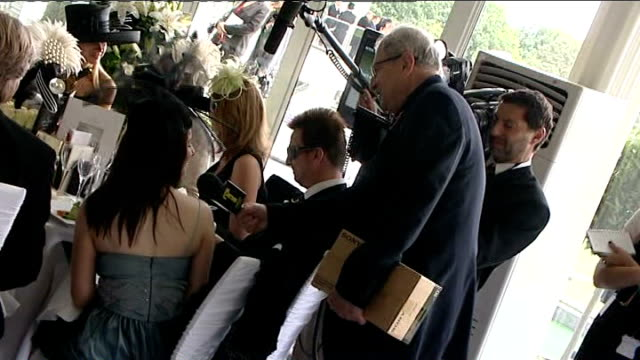 Attendees at Royal Ascot ENGLAND Berkshire Ascot Racecourse INT Smartly dressed racegoers inside marquee eating and chatting at round tables with...