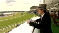 Attendees at Royal Ascot EXT Racegoers in top hats and fancy hats sip drinks by ornate carriages View of racecourse surveyed by unidentified man in...