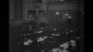 VS attendees seated at long tables at Committee for Industrial Organization with mounds of paper men hold papers upright hall decorated with American...