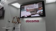 Attendees walk past the NTT DoCoMo Inc booth at the CEATEC Japan 2013 exhibition in Chiba City Japan on Wednesday Oct 2 The NTT DoCoMo Inc logo is...