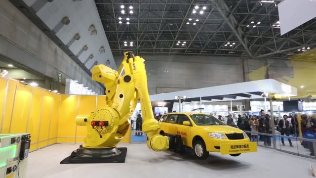 Attendees watch a Fanuc Corp industrial robot raise and lower a vehicle during a demonstration at the companys booth at the International Robot...