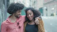 Aantrekkelijke Afrikaanse Amerikaanse echtpaar lopen en omarmen op stedelijke Street
