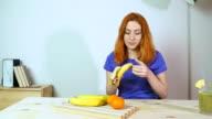 Attractive and fresh looking redhead girl at 20s eating banana