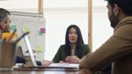 Attractive Asian woman leading business meeting
