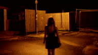 attractive beautiful young blonde woman in short skirt walks city street alone at night