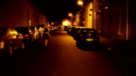 attractive beautiful young blonde woman walks alone in deserted city street at night