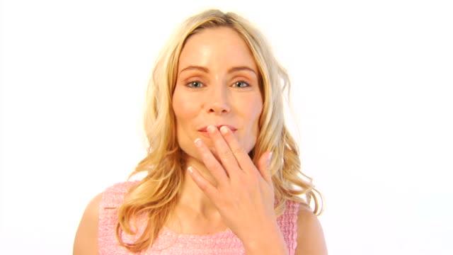 Attraktiven blonden Frau einen Kuss zuwerfen dann streicht Wellen