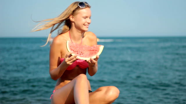 Attractive blond woman eating watermelon on beach