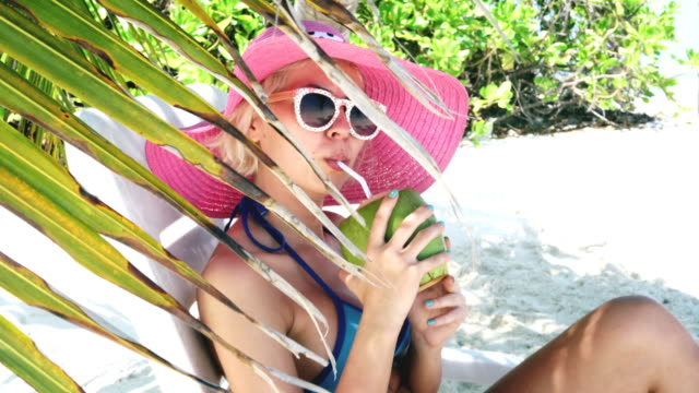 Attractive blonde woman under palm tree drinking coconut water, Maldives