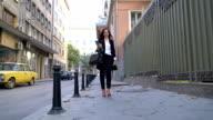 Attraktive Geschäftsfrau auf der Straße laufen, halten Dateiordner und Festsetzung ihrer Brille