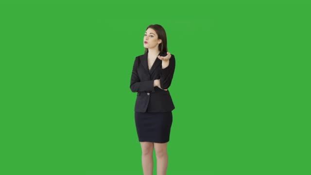 Attractive Caucasian Brunette Talking in Front of a Green Screen. Beautiful Businesswoman in Businesswear Standing against Green Backgound.