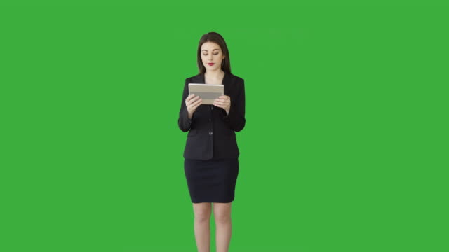 Attractive Caucasian Brunette Using Digital Tablet in Front of a Green Screen. Beautiful Businesswoman in Businesswear Standing against Green Backgound.