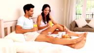 Attractive couple having breakfast in bed