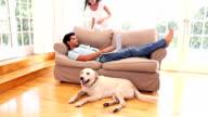 Coppia attraente rilassante in salotto con animale domestico labrador