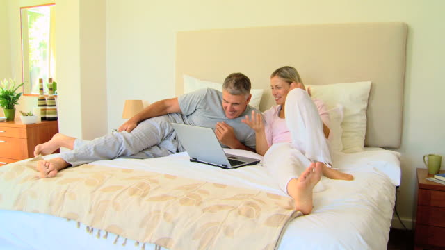 Attractive couple relaxing on bed with laptop / Cape Town, Western Cape, South Africa