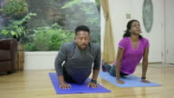 Attractive ethnic couple exercising together in their home