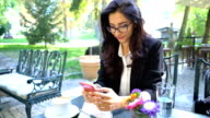Attractive female in business attire drinking coffee and browsing on the phone