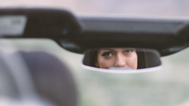 Attractive female looking in rearview mirror