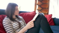 Attractive female reading a book while sitting on a sofa in the mountain cabin.