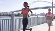 Attractive female runners in the city along the waterfront