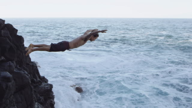 SLO MO Attractive male diving from cliff