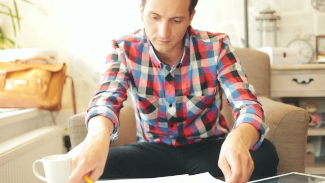 Attractive male working with digital tablet and plans.