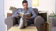 Attractive man reading a book at home