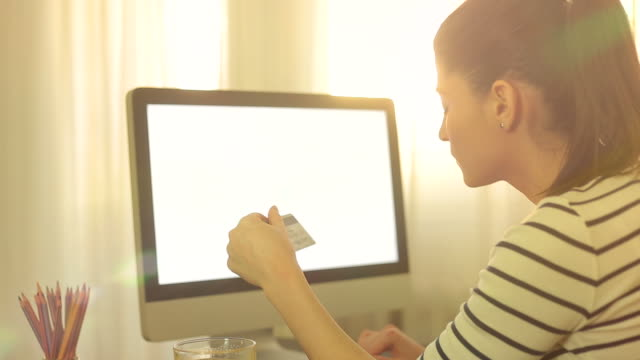 Attractive woman buying online with her credit card using the computer.