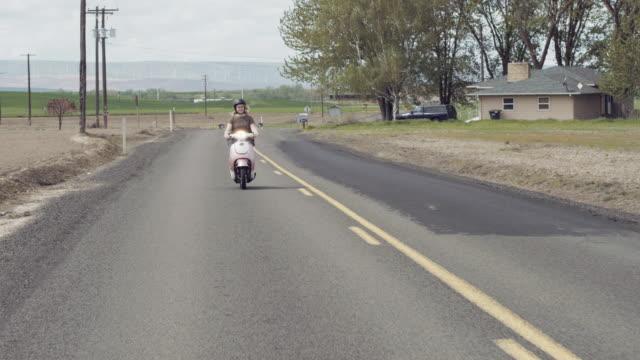 Aantrekkelijke vrouw rijden op scooter landelijke weg