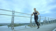 Attractive woman running in the city across a bridge