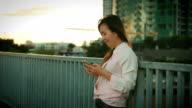 Attraktive Frau mit Handy während zu Fuß, auf Straßen der Nacht Stadt