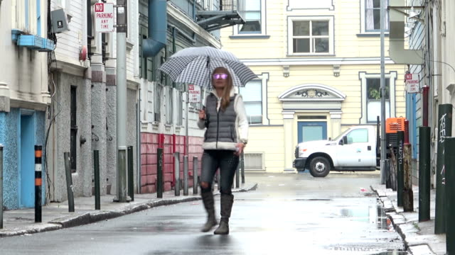 Attractive Woman with an umbrella is walking out into a charming alley on a rainy day. Checking her mobile phone.
