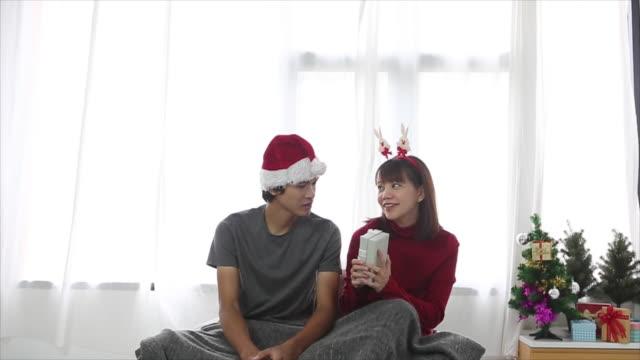 Aantrekkelijke jonge Aziatische paar dragen van santa hoeden met cadeau