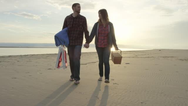Attraente Giovane coppia romantica avendo un pic-nic sulla spiaggia, un piedi nel al rallentatore