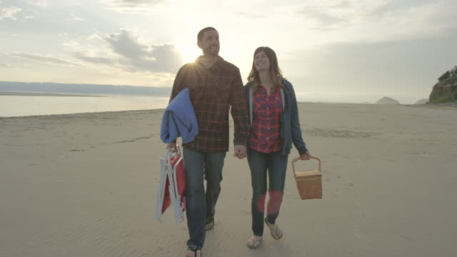 Attractive young couple having a romantic picnic on the beach; walking in slow motion