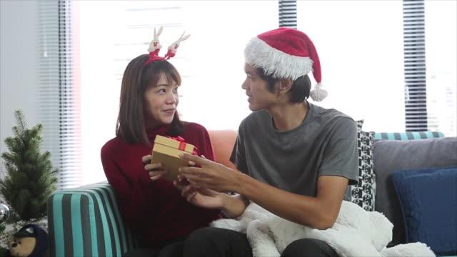 Aantrekkelijke jonge paar dragen van santa hoeden met cadeau