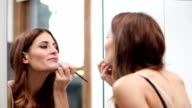 Attractive young lady applying lip-gloss/lipstick night out